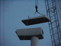 The lid to the nacelle is lifted to the top and placed on the nacelle. Aug. 21, 2003.