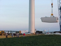 Workers hold onto the ropes to hold the nacelle straight as it's lifted. Aug. 21, 2003.